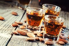 Italian amaretto liqueur with dry almonds on the old wooden back. Ground, selective focus royalty free stock photography