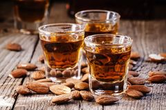 Italian amaretto liqueur with dry almonds on the old wooden back royalty free stock photography