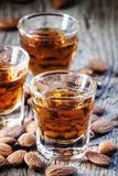 Italian amaretto liqueur with dry almonds on the old wooden back royalty free stock image