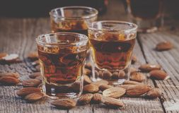 Italian amaretto liqueur with dry almonds on the old wooden back royalty free stock photo