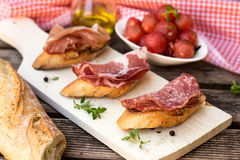 Italian antipasti bruschettas with ham prosciutto, coppa and sal Royalty Free Stock Images
