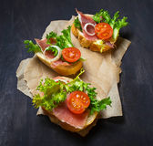 Italian antipasti crostini with ham, salad and tomato. Traditional Italian antipasti crostini with ham, salad and tomato. Selective focus Stock Image
