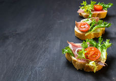 Italian antipasti crostini with ham, salad and tomato. Traditional Italian antipasti crostini with ham, salad and tomato. Selective focus. Space for text Royalty Free Stock Photography