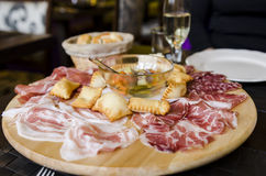 Italian antipasti on table. A table set for two with Italian antipasti; Torta fritta, Parma ham, prosciutto and other cured meats and vegetables in oil Stock Photo