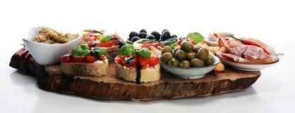 Italian antipasti wine snacks set. Cheese variety, Mediterranean olives, pickles, Prosciutto di Parma, tomatoes, artichokes royalty free stock photo