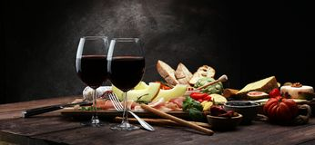 Italian antipasti wine snacks set. Cheese variety, Mediterranean. Olives, pickles, Prosciutto di Parma with melon, salami and wine in glasses over black grunge royalty free stock image