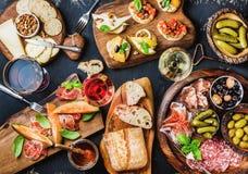 Italian antipasti wine snacks set over black grunge background Stock Images