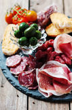 Italian antipasto. Antipasto with ham, olive and tomato on the wooden table, selective focus Royalty Free Stock Photos