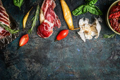 Italian antipasto snack with smoked meat, tomatoes and ciabatta bread on rustic background, top view Royalty Free Stock Photos