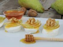 Italian antipasto snacks with mozzarella, pear, honey and walnuts stock photo