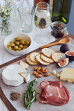 Italian appetisers. Selection of gourmet cured meat charcuterie salami, coppa, with brie camembert gruyere cheese served with olives nuts and fruit Royalty Free Stock Photo