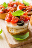 Italian Appetizer Bruschetta. With roasted tomatoes, mozzarella cheese, garlic and herbs Stock Photos