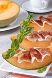 Italian appetizer: melon with ham vertical close up. Italian appetizer: melon with ham on a white plate. vertical close up Royalty Free Stock Image