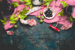 Italian appetizer snack on red cell cotton tablecloths with salami, olives and red wine, dark rustic background Stock Photo