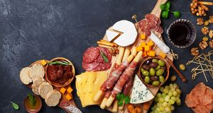 Italian appetizers or antipasto set with gourmet food on black table top view. Delicatessen of cheese and meat snacks with wine. Italian appetizers or antipasto stock images