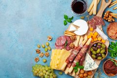 Italian appetizers or antipasto set with gourmet food on blue table top view. Mixed delicatessen of cheese and meat snacks royalty free stock image