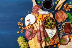 Italian appetizers or antipasto set with gourmet food on wooden kitchen table top view. Delicatessen of cheese and meat snacks. Italian appetizers or antipasto royalty free stock photos