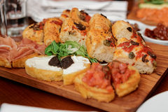 Italian appetizers on wooden plank Stock Photography