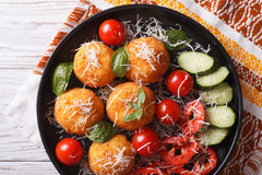Italian arancini rice balls with cheese close-up. horizontal top. Italian arancini rice balls with cheese and fresh vegetables on the plate close-up. horizontal Stock Image