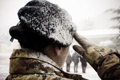 Italian army woman under the snow. Italian army female soldier who are doing an military salute Stock Image