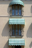 Italian balconies. Facade of an old hotel with striped awnings in Garda, Italy Royalty Free Stock Image