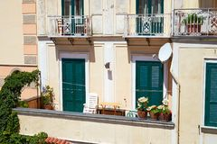 Italian balcony with flowers and closed green shutters Royalty Free Stock Photography