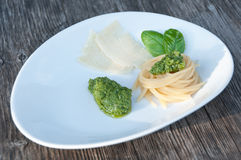 Italian basil pesto with spaghetti and parmesan. On a white plate Royalty Free Stock Photography