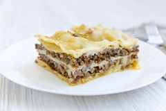 Italian beef lasagne on a white round plate, close-up. White wooden background. Side view stock images