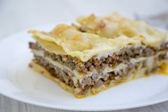 Italian beef lasagne on a white round plate, white wooden background. Side view Stock Photo