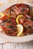 Italian beef Saltimbocca with sage, ham and lemon close-up. Vert Royalty Free Stock Photo