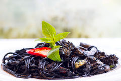 Italian black spaghetti with squid rings and mussels. Stock Photo