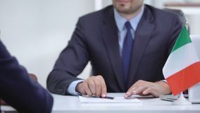 Italian boss signing employment contract with immigrant employee, shaking hand. Stock footage stock footage