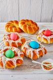 Italian braided Easter Bread Rings, top view. Individual sweet Italian braided Easter Bread Rings glazed around dyed egg and topped with colorful sprinkles on a stock photos