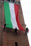 Italian brave firefighters climb the old tower with a giant Ital. Italian fearless firefighters climb the old tower with a huge Italian flag Stock Photo