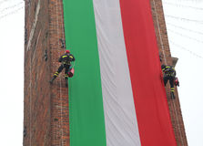Italian brave firefighters climb the old tower with an Italian f. Italian brave fearless firefighters climb the old tower with a giant Italian flag Stock Image