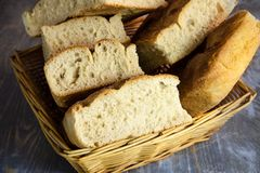 Italian bread of Focaccia Genovese type on display on a basket on a rustic wooden table, sliced in several squared pieces. The focaccia is a traditional oven royalty free stock photography
