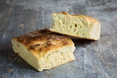 Italian bread of Focaccia Genovese type on a rustic wooden table, sliced in two squared pieces. The focaccia is a traditional oven baked flat bread, this one stock photography