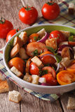 Italian bread salad - panzanella close-up on the table. Vertical Stock Image
