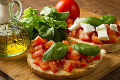 Italian bruschetta. With fresh tomatoes, basil, garlic, olive oil and cheese Royalty Free Stock Photos