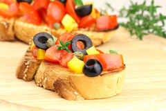 Italian bruschetta. Close up of Italian bruschetta with tomatoes, bell pepper, black olives and capers Royalty Free Stock Photo