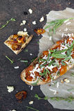Italian bruschetta with baked cherry tomatoes, parmesan cheese and rocket on toasted bread Stock Photo