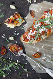 Italian bruschetta with baked cherry tomatoes, parmesan cheese and rocket on toasted Royalty Free Stock Photo