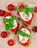 Italian bruschetta with cherry tomatoes, mozzarella & fresh basil. Stock Image