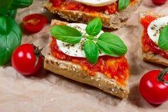 Italian bruschetta with cherry tomatoes, mozzarella & fresh basil. Royalty Free Stock Photo