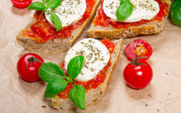 Italian bruschetta with cherry tomatoes, mozzarella & fresh basil. Stock Images