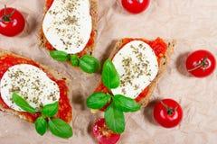 Italian bruschetta with cherry tomatoes, mozzarella & fresh basil. Stock Photography