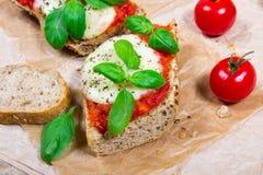Italian bruschetta with cherry tomatoes, mozzarella & fresh basil. Stock Photo