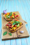 Italian bruschetta with chopped tomatoes and basil on wooden cutting board Stock Photography