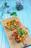 Italian bruschetta with chopped tomatoes and basil on wooden cutting board Stock Photo