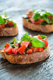 Italian bruschetta with chopped vegetables, herbs and oil on gr Royalty Free Stock Photography